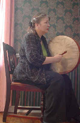sitting, holding the bodhran facing the other way
